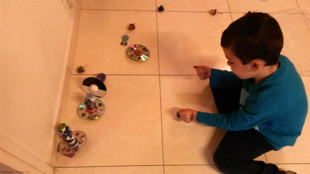 אורי נכדי נהנה מהסביבונים הזוהרים שיצר מחומרים ממוחזרים