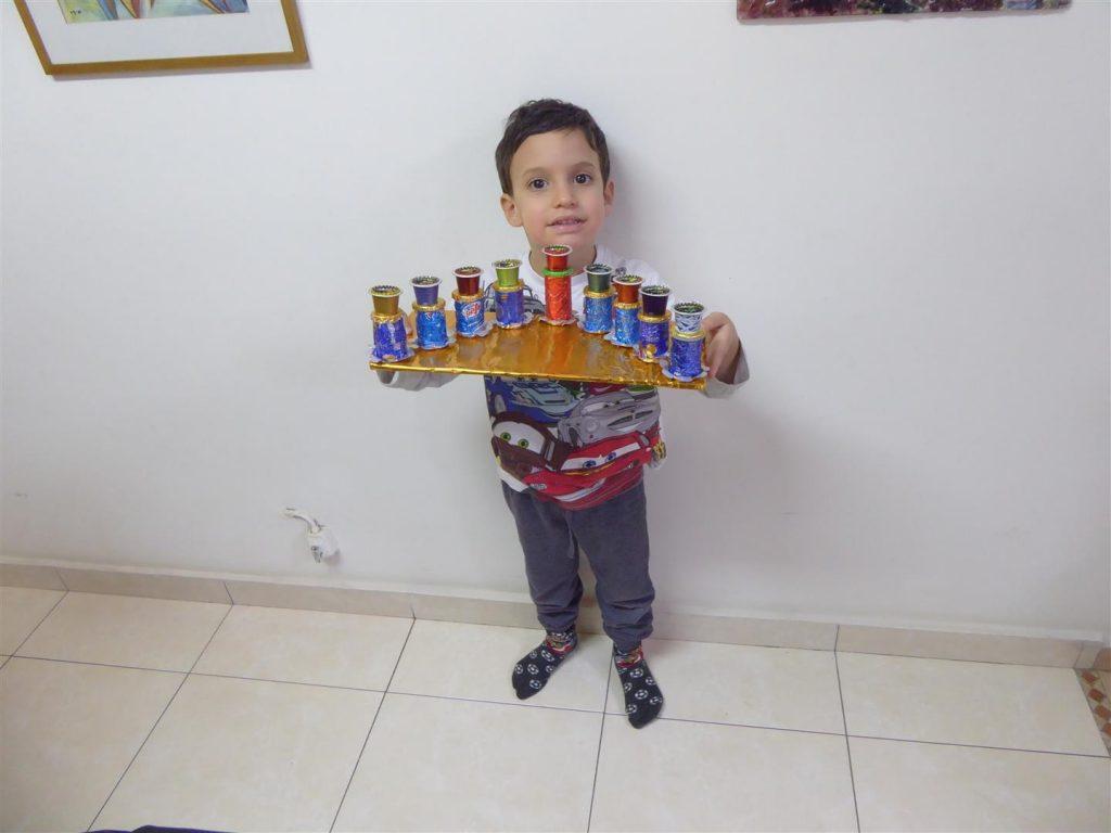 יואבי נכדי עם החנוכייה הזוהרת שיצר מאריזות הממתקים שאספו בבית
