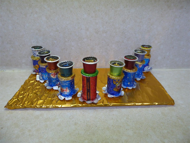 חנוכייה מחומרים ממוחזרים של אריזות ממתקים, נרונים פקקים וקפסולות של קפה