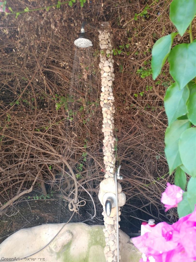 צינור מקלחת מעוטר באבנים מהטבע -אמנות אקולוגית במיצב סיפור גן העדן