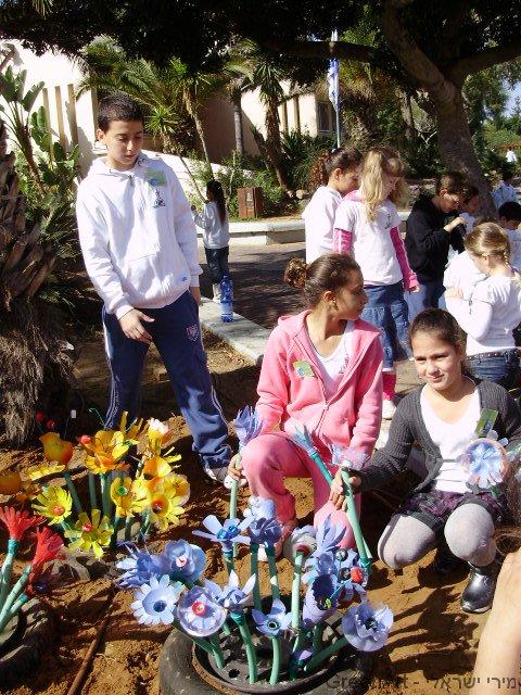 תלמידי בית ספר ויצמן שותלים את הפרחים בתות צמיגים ישנים