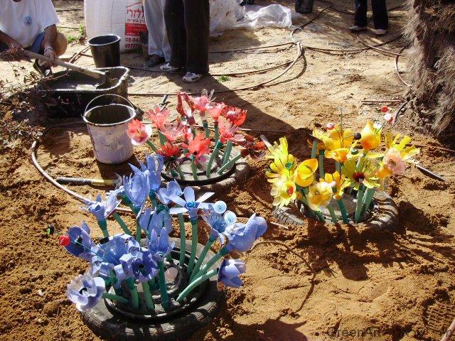 אדניות מצמיגים ישנים המעוצבים בשלל פרחים צבעוניים