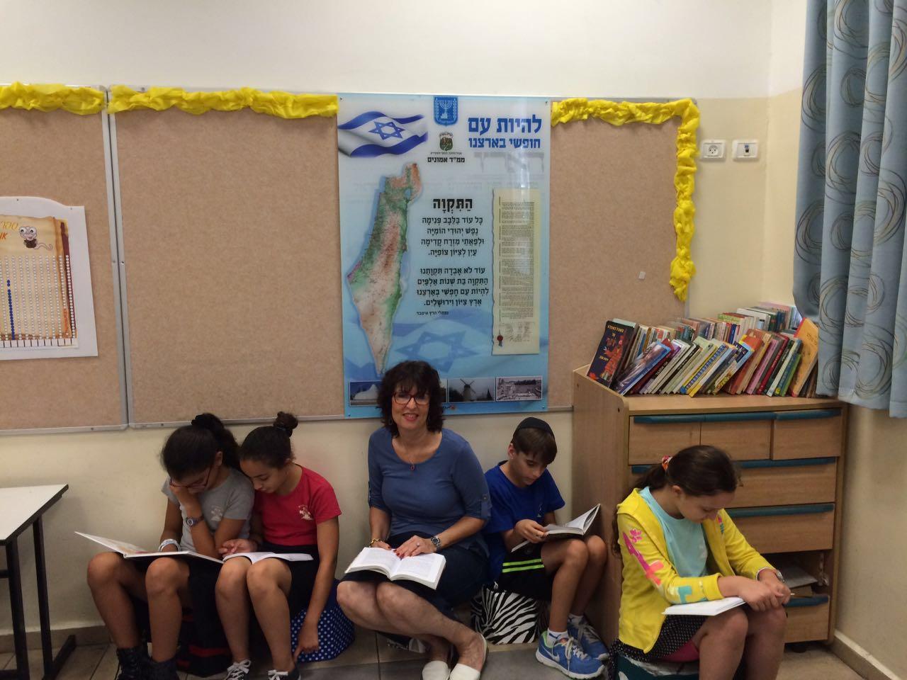 המורה שוש גוטמן עם תלמידיה נהנים מפרי יצירתם בפינת הישיבה החדשה