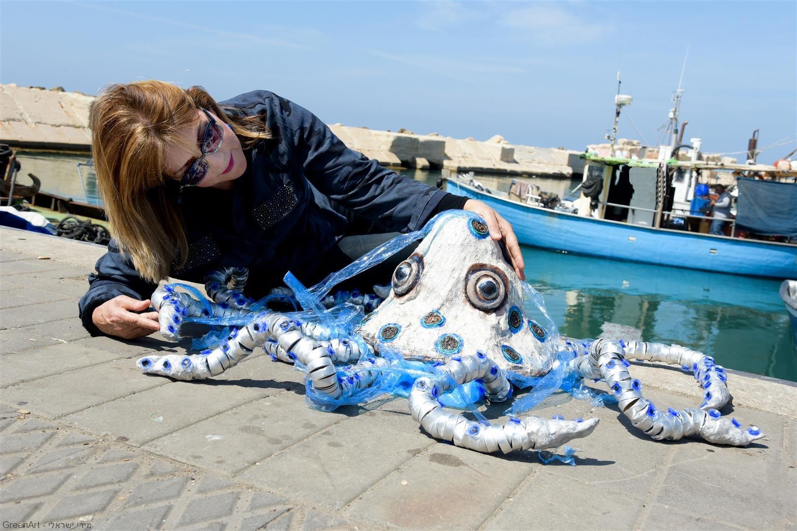 מפגינה אהבה לתמנון הפגוע קשות משקיות הניילון החונקות את גופו- אמנות אקולוגית מפסולת