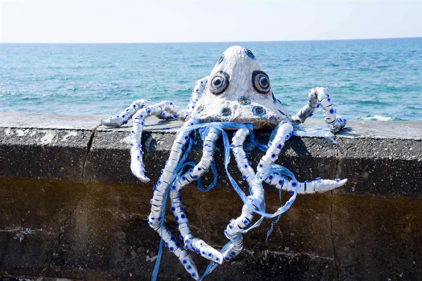 התמנון מגיע מהים עם שקיות ניילון החונקות אותו עם מסר לאדם לשמור על היצורים הימיים