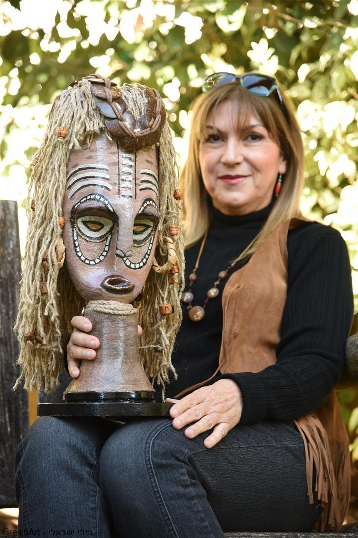 מירי ישראלי עם המסכה האפריקאית המפוסלת  מחומרים ממוחזרים - אמנות אקולוגית בעלת מסר לחברה