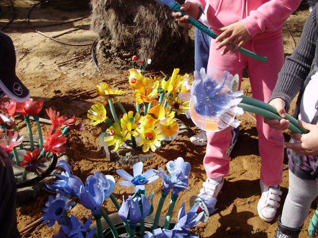 חצר פרחוני מאדניות של צמיגים ישנים המעוצבים בשלל פרחים צבעוניים