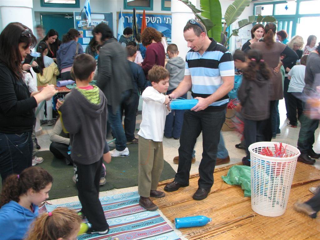 שיתוף פעולה יצירתי בין הורים וילדים ליצירת מאות פרחים מבקבוקי פלסטיק