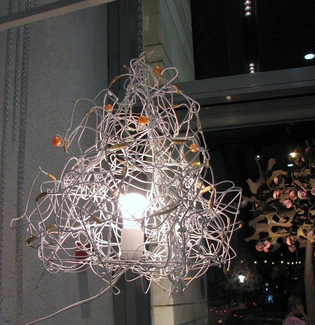 מנורה מפוסלת מקולבי מתכת מעוטרים בניירות מוזהבים של ממתקים