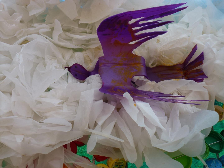 ציפור במעופה מבקבוק פלסטיק סגול על ענן משקיות ניילוןלבנות