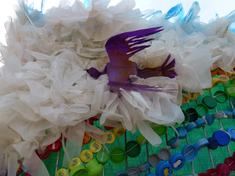 ציפור במעופה מבקבוק פלסטיק סגול על ענן משקיות ניילון