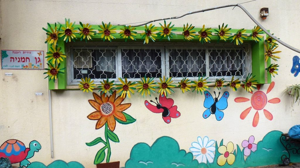 חזית החלון עם החמניות הצבעוניות המדגישות את יופי היצירה מפסולת האדם