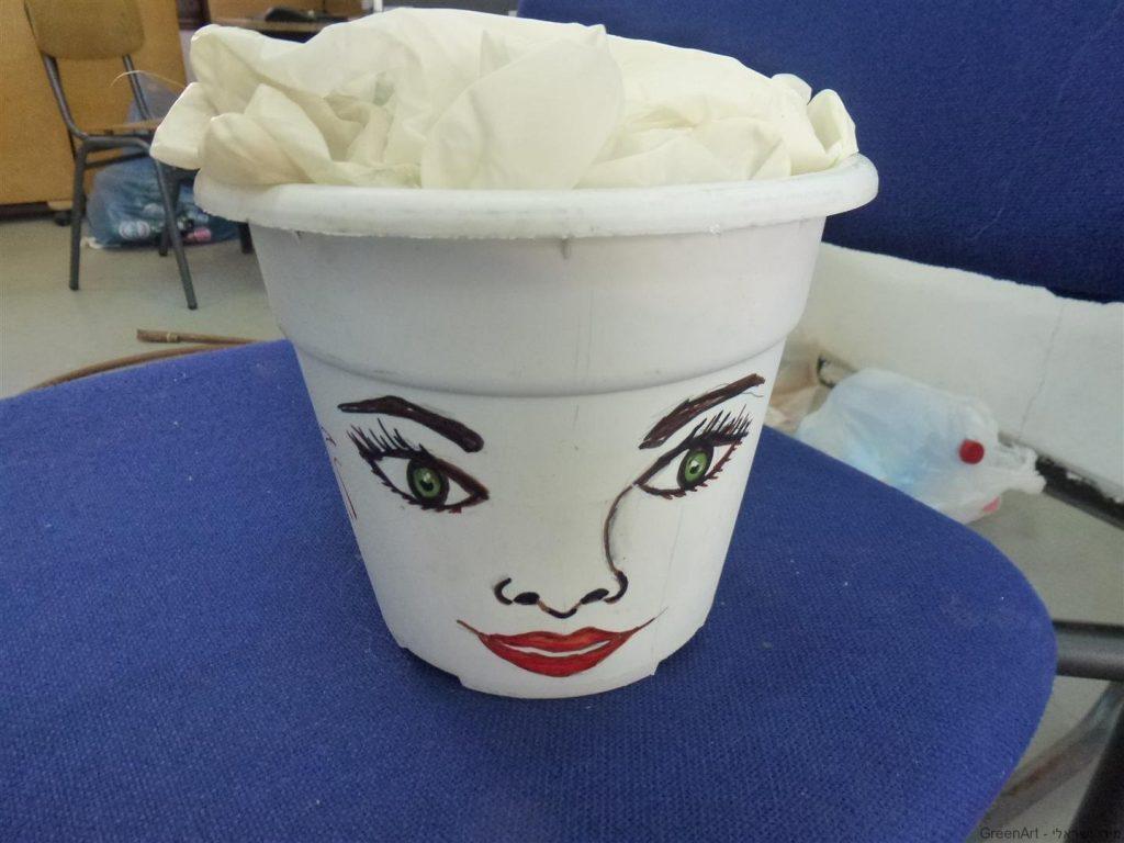 פנים מצוירות על עציץ פלסטיק בשימוש חוזר