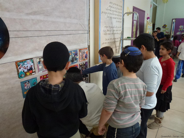 תלמידי אושא נרגשים לראות את היצירות שלהם  מתקבצות לשטיח