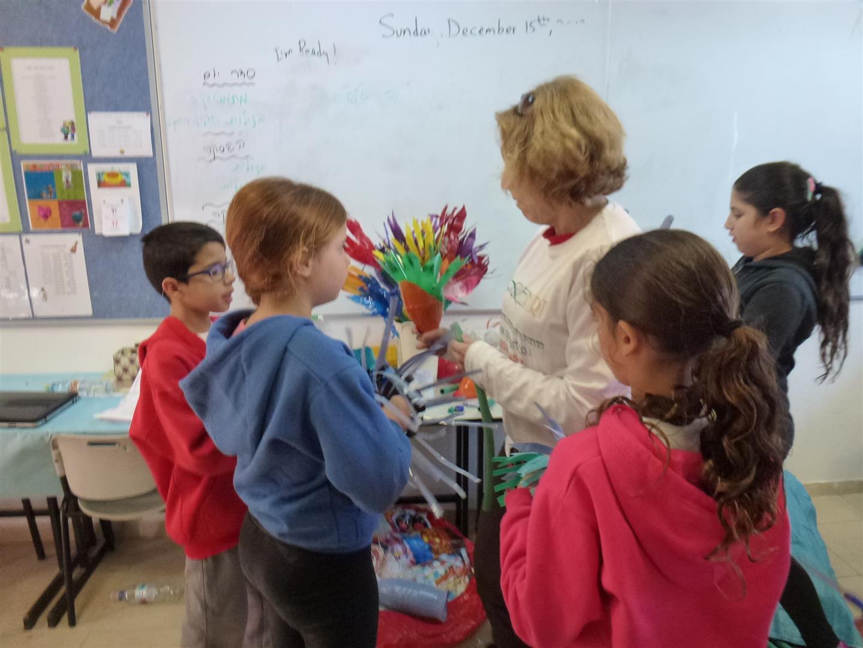 דפנה מדריכה את התלמידים כיצד לעצב פרחים מבקבוקים שונים