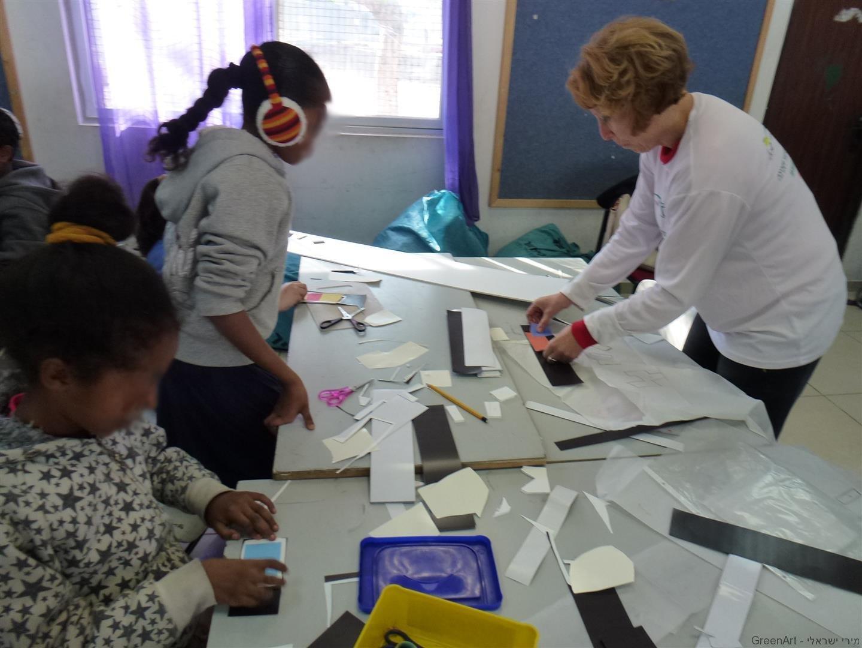 תלמידות שכבת ה' נהנות לגזור את המגנטים לעיצוב המיצב הסביבתי