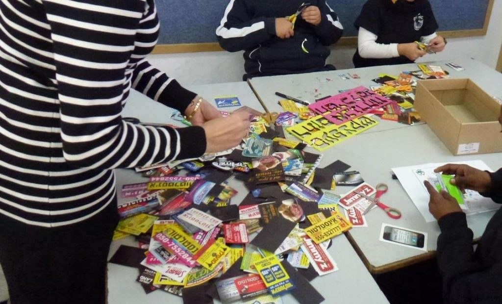 תלמידי שכבת ה' מחפשים מגנטים צבעוניים לעיצוב הכיתובים