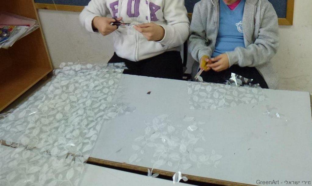 תלמידות נהנות לגזור מפות ישנות ולשלב את העלים בעיצוב מסגרת המיצב