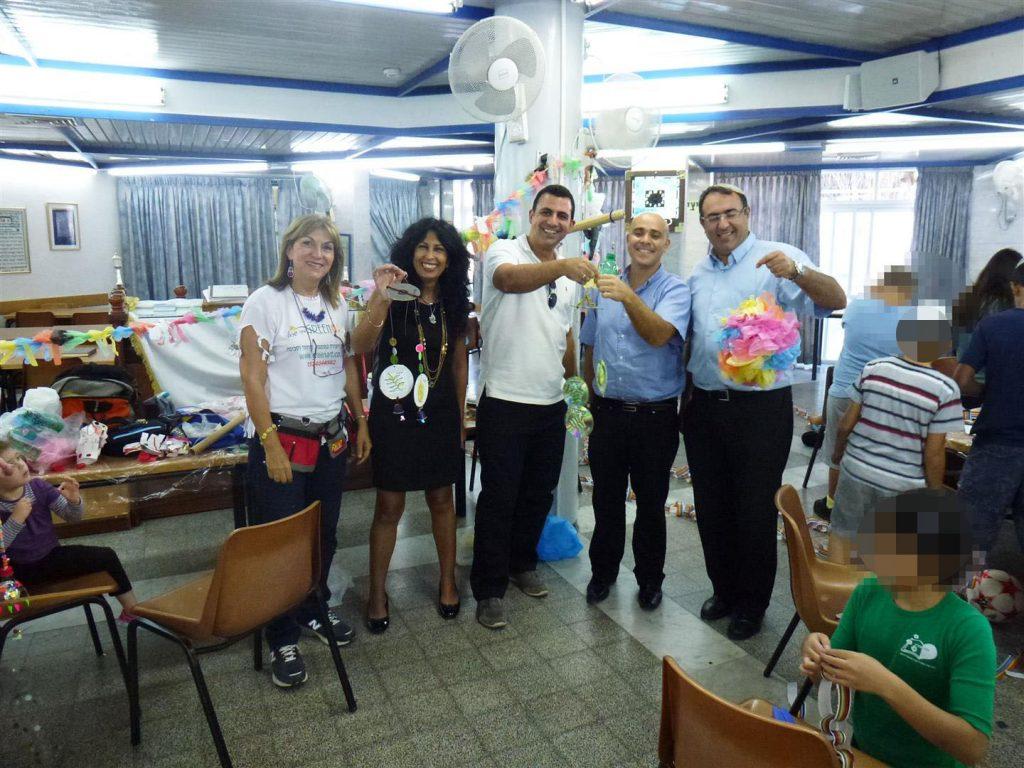 מתנדבי בנק לאומי לשמכנתאות עם הקישוטים המרהיבים לסוכה הירוקה