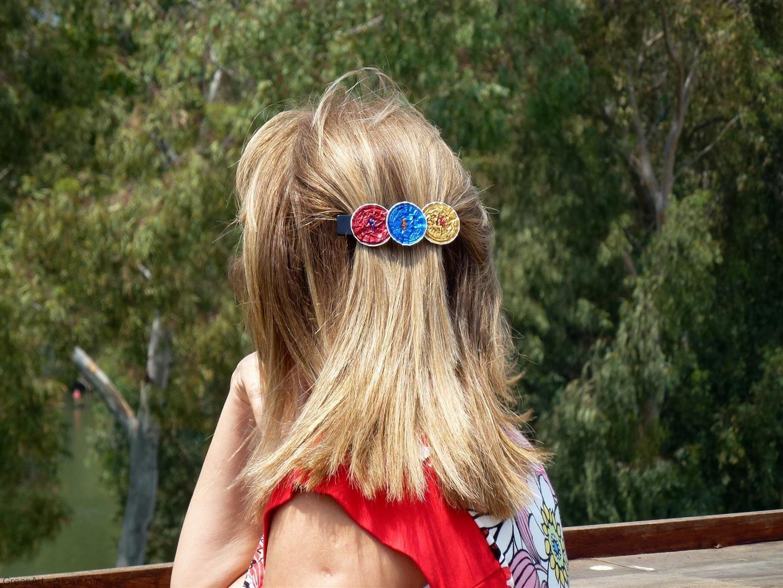 מביטה בהנאה לנוף הנישקף ומדגמנת סיכת שיער תוצרת עצמית המוצעת בחנות המרכז