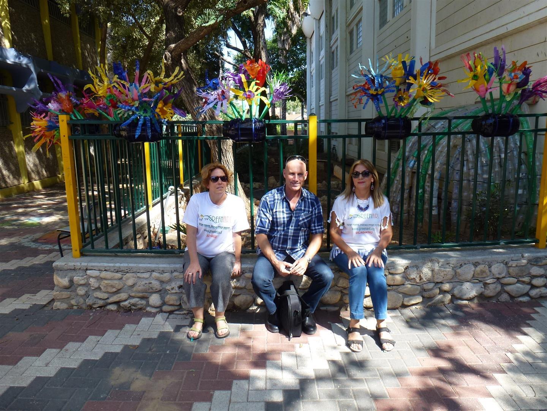 אני דפנה ויהונתן  מנהל בית הספר אמיר פתח תקוה לאחר ביצוע עיצוב חצר בית הספר באדניות פרחוניות מבקבוקי פלסטיק
