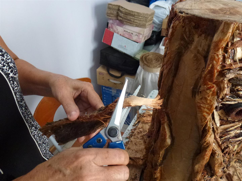 שלב הדבקת מאות פיסות מקליפות עץ קטנות לחיפוי הגליל קרטון עם השורשים