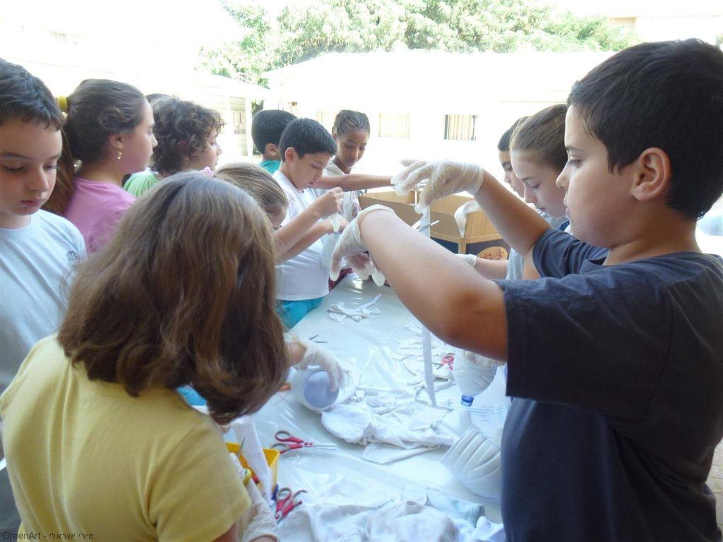 תלמידי שכבת כיתות ה' גוזרים פילטרים לתוך מתקני העציצים.