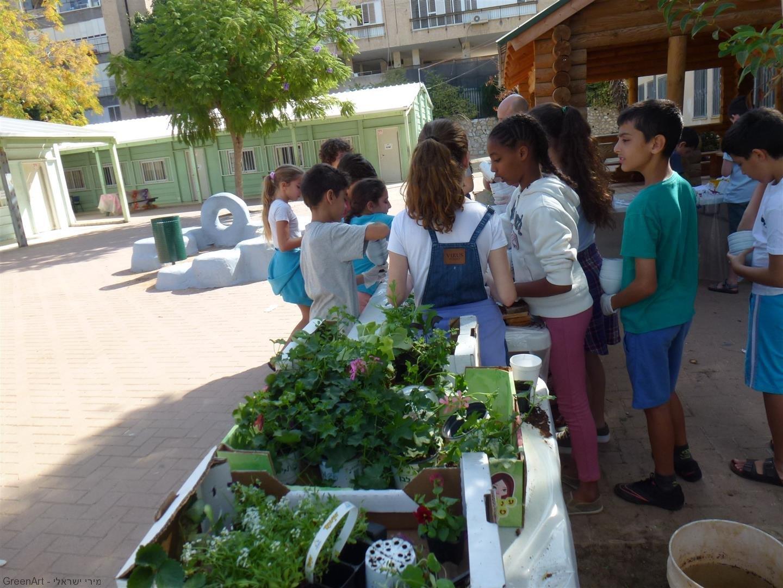 תלמידי ברטוב שותלים צמחים ופרחים בתוך בקבוקי הפלסטיק