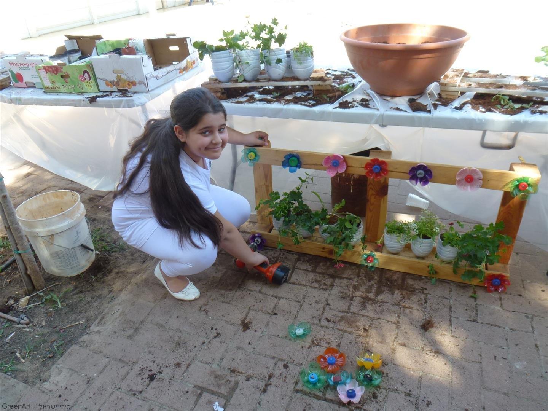 התלמידות נהנות להבריג את הפרחים לקורות העץ לעיצוב האדניות