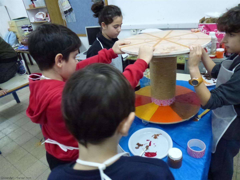 צוות  התלמידים המציירים ומעצבים את השולחן נהנים מתהליך הצביעה