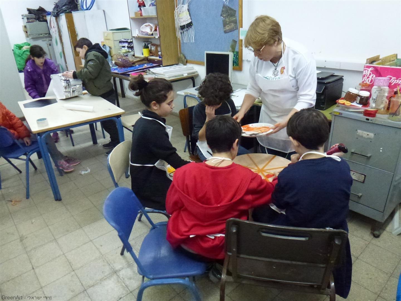 דפנה מדריכה את צוות התלמידים המציירים ומעצבים את השולחן נהנים מתהליך הצביעה