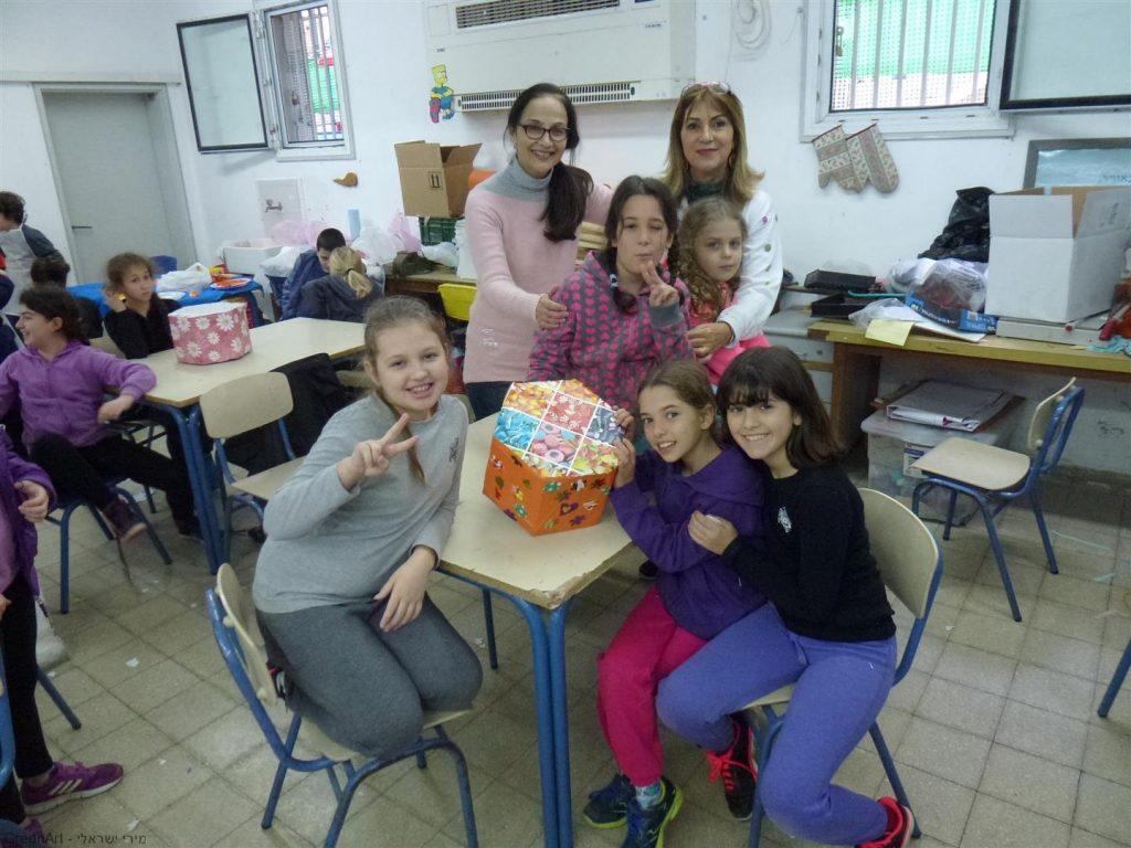 תלמידות שכבת ד' והמחנכת נהנות מפרי יצירתן שרפרף בעיצוב סוכריות צבעוניות ועליזות.