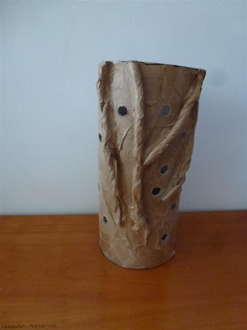 גליל קרטון חלול ששימש לפיסול המיצב המואר מעוטר בפסולת ניירות אריזה, זכוכיות ומקשי מקלדת שחורה