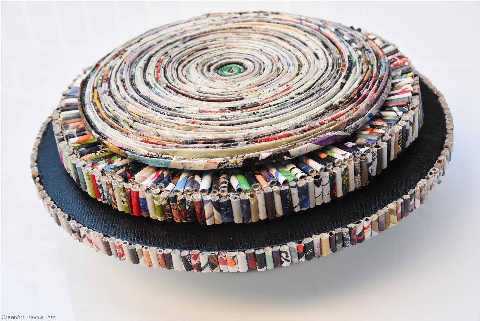 גלילי נייר צבעוניים שפוסלו לספרילה מעגלית המסתובבת על צירה. eco art.